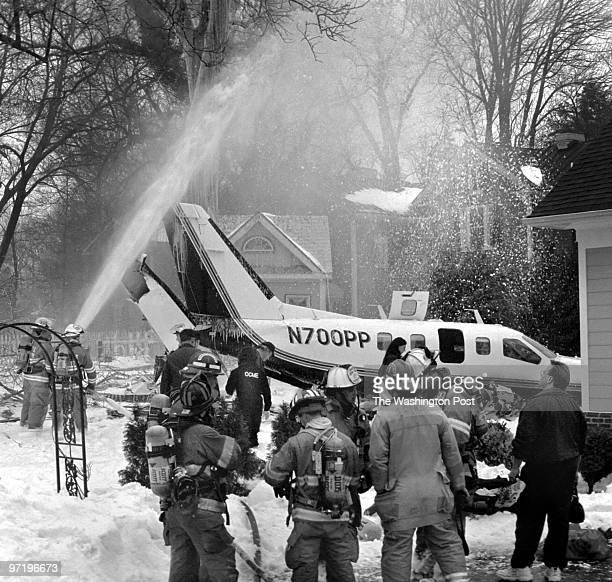 ME/Crash Fire personnel spray foam on the crash area where a Lear Jet crashed into the backyard of a residential neighborhood in Leesburg VA killing...