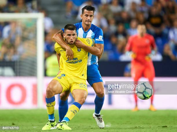 SLuis Hernandez of Malaga CF competes for the ball with Jonathan Calleri of Union Deportiva Las Palmas during the La Liga match between Malaga and...