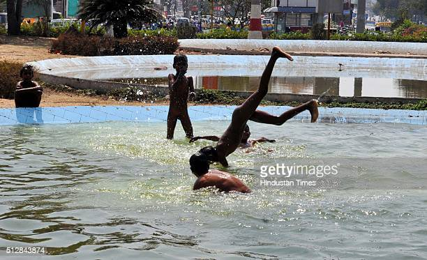 Slum children jump into a water pool situated inside Vijay Nagar rotary to beat the heat on February 28 2016 in Indore India Searing heat continued...