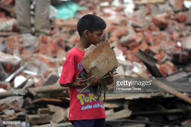 MUMBAI INDIA MAY 27 2006 Slum Demolition 9 year old lacchu yadav picks up remnants from his demolished house in Valnai colony where the BMc...