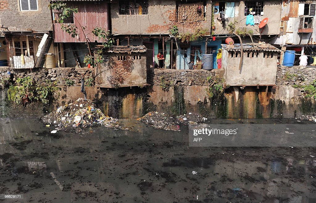 Slum dwellers look out from their homes adjacent to a sewage drain in Dharavi, Asia's biggest slum area, in Mumbai on April 20, 2010. AFP PHOTO/Punit PARANJPE