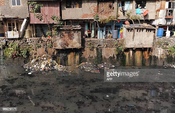 Slum dwellers look out from their homes adjacent to a sewage drain in Dharavi Asia's biggest slum area in Mumbai on April 20 2010 AFP PHOTO/Punit...