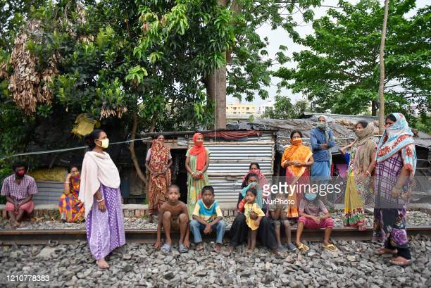 Slum dwellers sit beside a railway track during a nationwide lockdown to slow the spreading of the coronavirus disease Kolkata India 23 April 2020...