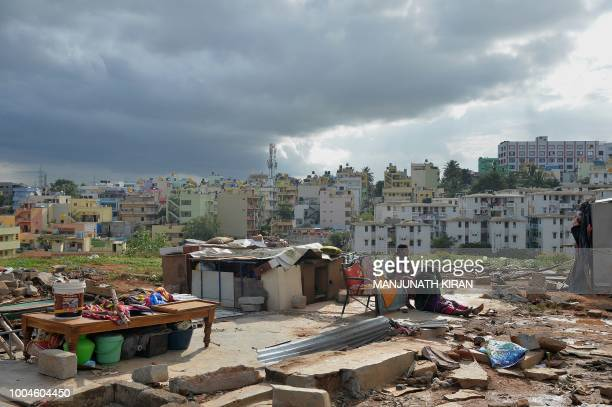 Slum dwellers sit by the remains of a shelter amidst the ruins of a slum in Banglore on July 24 after it was razed by the Karnataka Slum Clearance...