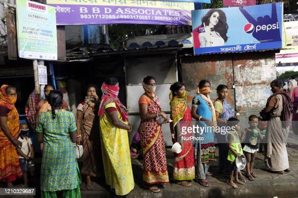 Slum People wait in a queue to receive free food outside Railway Station area during a lockdown in Kolkata India on April 17 2020 Indian Prime...