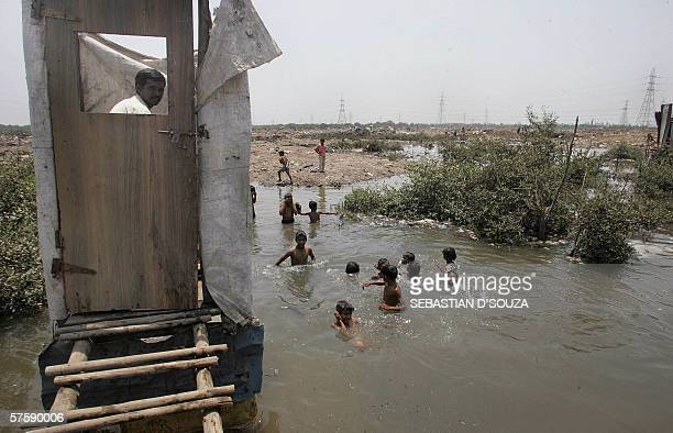 A slum resident uses a toilet that opens into the water below as children swim in the water near a protest rally against the government for...