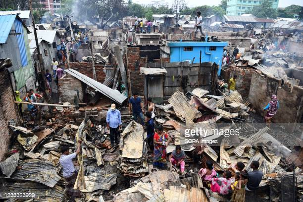 Slum-dwellers search for their belongings after a fire swept through the slum. Several hundreds of houses were gutted as the devastating fire that...