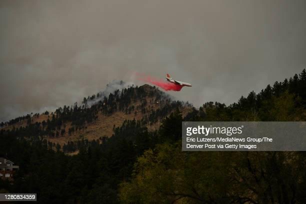 Slurry bomber drops retardant over the CalWood fire near Buckingham Park northwest of Boulder on Saturday October 17, 2020. Photo by Eric...