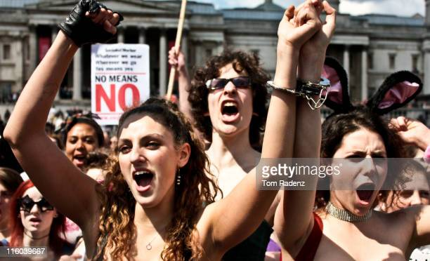 'Slutwalk' - Women against rape, London June 2011. Two women and a man with the crowd behind them cheering at Trafalgar Square.