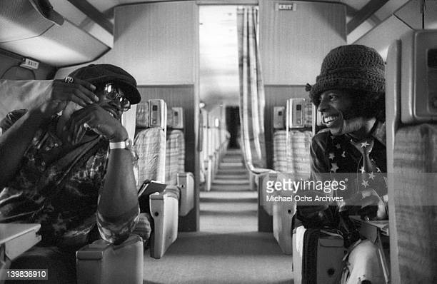 Sly Stone of the psychedelic soul group 'Sly and the Family Stone' talks with a man as they sit aboard a plane in San Diego to do a radio interview...