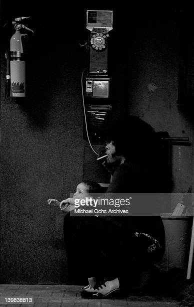Sly Stone of the psychedelic soul group 'Sly And The Family Stone' talks on a pay phone as he plays with his niece during a recording session on...