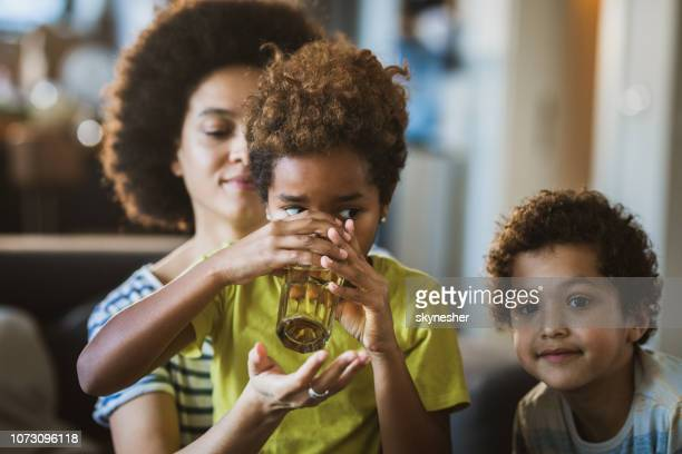 small african american girl drinking water with assistance of her mother. - drinking water stock pictures, royalty-free photos & images
