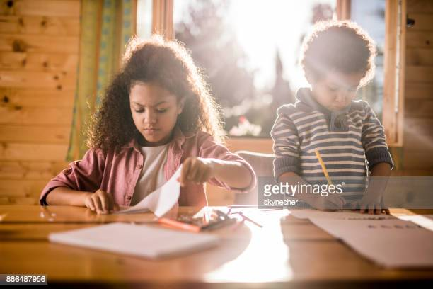 Small African American kids having a creative time at home.