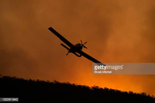 A small aircraft is pictured after dumping fire retardant behind houses at the foot of Mount Tennant as the fire front of the Orroral Valley fire...