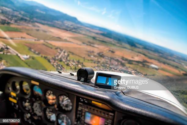 small airplane cockpit interior in selective focus with control instrument panel and hilly landscape background in summer - cockpit stock pictures, royalty-free photos & images