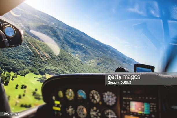 Small airplane cockpit interior in selective focus with control instrument panel and hilly landscape background in summer