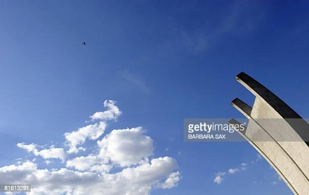 "Small airplane flies over the airlift memorial nicknamed ""Hungerkralle"" near Tempelhof airport in Berlin on June 17, 2008. During the Berlin..."