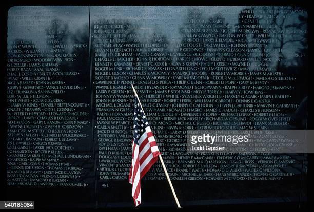Small American Flag Waving In Front of Vietnam Veterans Memorial