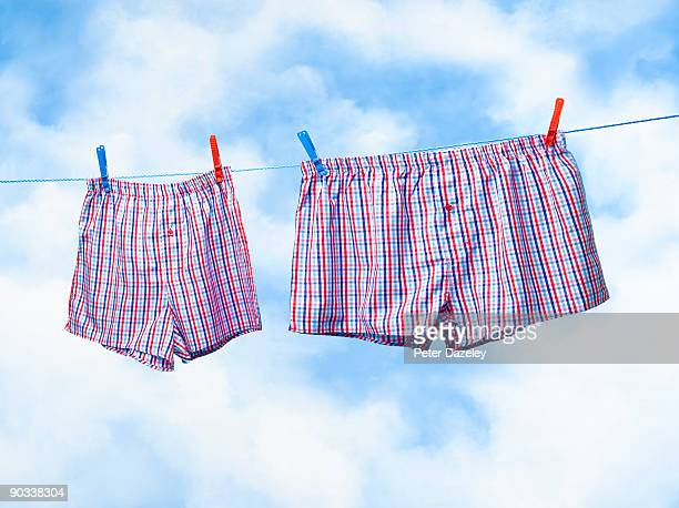 small and obese boxer shorts on washing line. - boxershort stock pictures, royalty-free photos & images
