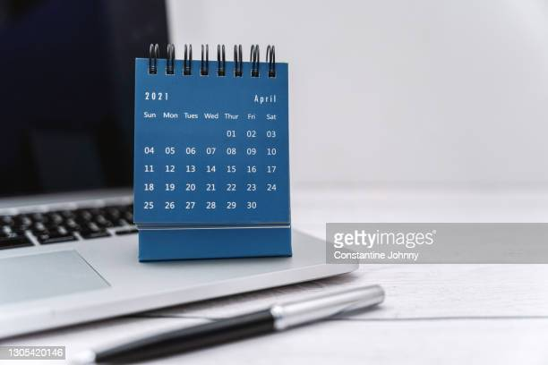small april 2021 desk calendar on laptop on top of white painted wooden desk - 四月 ストックフォトと画像