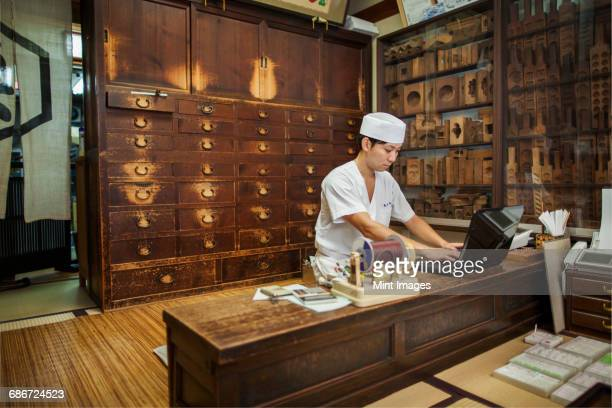 a small artisan producer of specialist treats, sweets called wagashi. a cook using a laptop and making a phone call at a desk.  - wagashi stock pictures, royalty-free photos & images