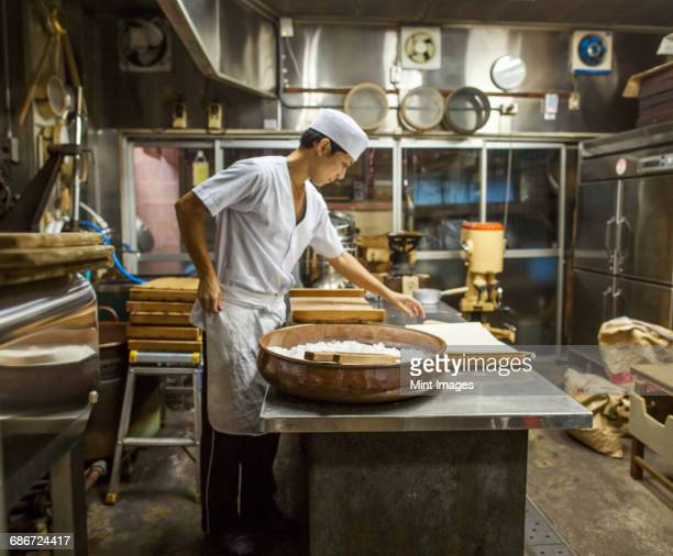a small artisan producer of wagashi. a man mixing a large bowl of ingredients and pressing the mixed dough into moulds in a commercial kitchen. - preparation ストックフォトと画像