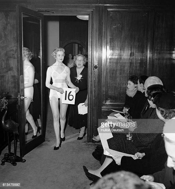A small audience looks on as a model enters the showroom wearing a brassiere and girdle ca 1955