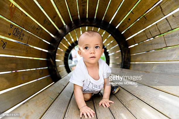 Small baby boy walking in playground tunnel