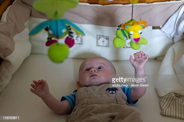 small baby in cradle with hanging toys - s0ulsurfing stock pictures, royalty-free photos & images