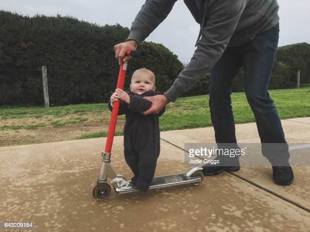 Small baby riding a scooter with help from father