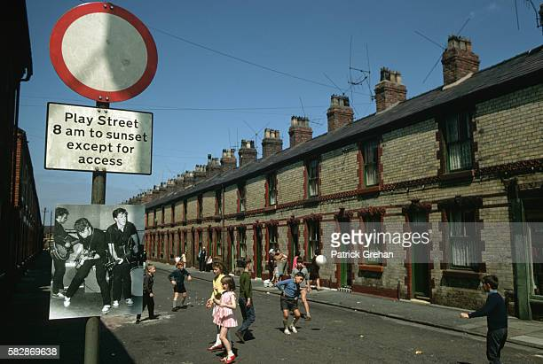A small Beatles poster hangs on the traffic sign marking a street that is reserved for playing children during the day