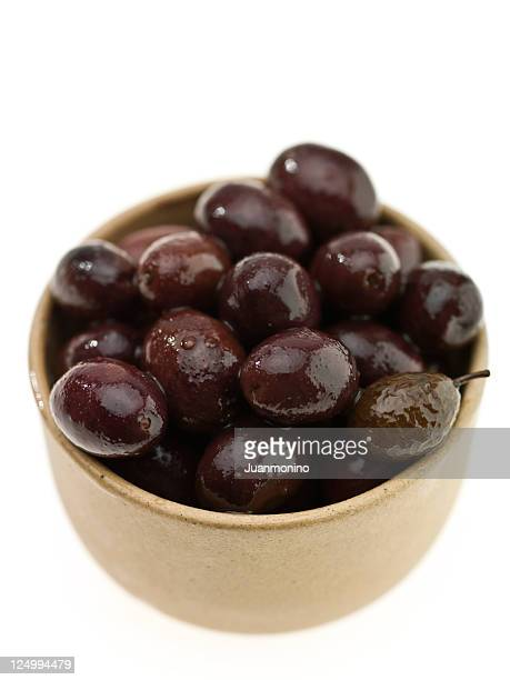 small beige bowl of nicoise olives on a white background - kalamata olive stock pictures, royalty-free photos & images