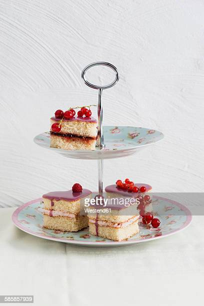 Small biscuit cakes in heart shape with raspberry cream and currant jelly, cake stand