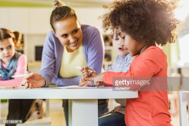 small black girl coloring with her friends and teacher at preschool. - child care stock pictures, royalty-free photos & images