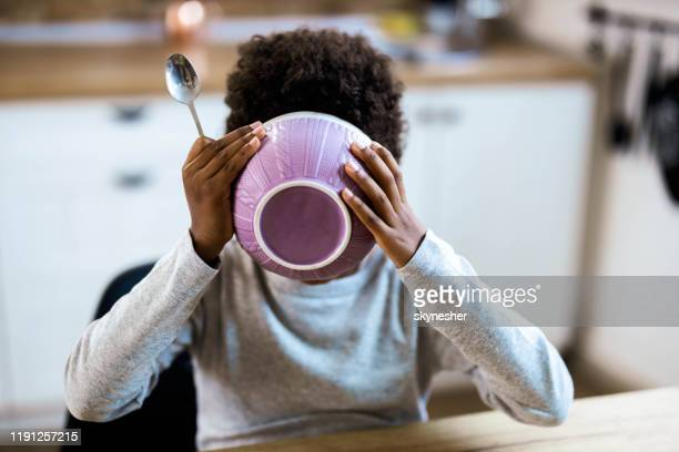 small black kid eating his breakfast from a bowl at dining table. - breakfast cereal stock pictures, royalty-free photos & images