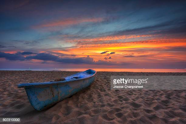 A small blue boat with Sunset At Karon Beach Phuket , Thailand