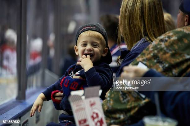 A small Blue Jackets fan smiles during a game between the Columbus Blue Jackets and the Caroling Hurricanes on November 10 at Nationwide Arena in...