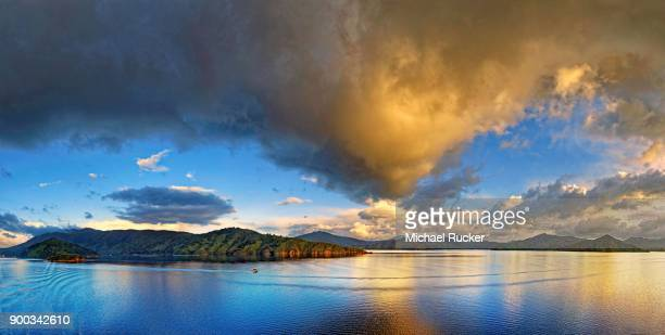 Small boat at sunrise, cloudy sky in Queen Charlotte Sound, Marlborough Sounds, Picton, South Island, New Zealand