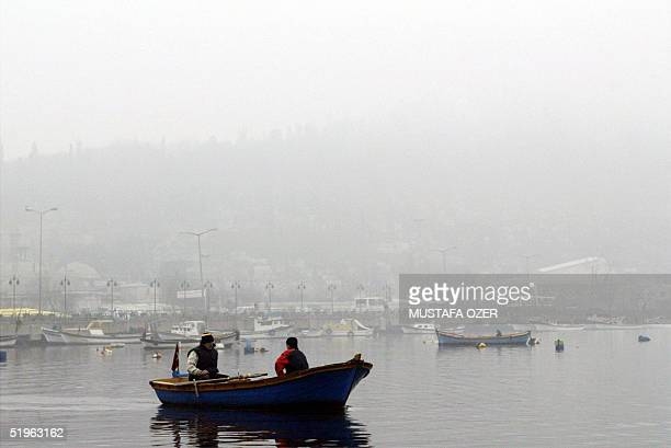 A small boat carries passangers at the Golden Horn on a fogy day in Istanbul 14 January 2005 Heavy fog distracts the sea traffic along Dardanelles...