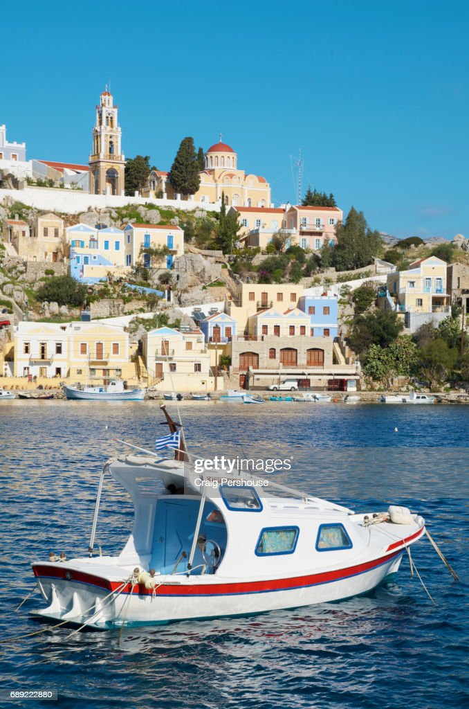 Small boat in Symi Harbour before pastel-coloured houses and Ekklisia Evaggelistria (Annunciation Church). : Stock Photo