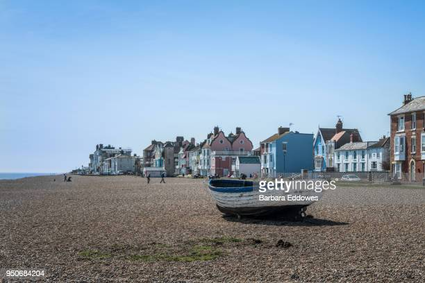 a small boat on a beach with houses in the background in aldeburgh, suffolk - suffolk england stock photos and pictures