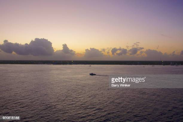 Small boat on calm Caribbean waters at dusk