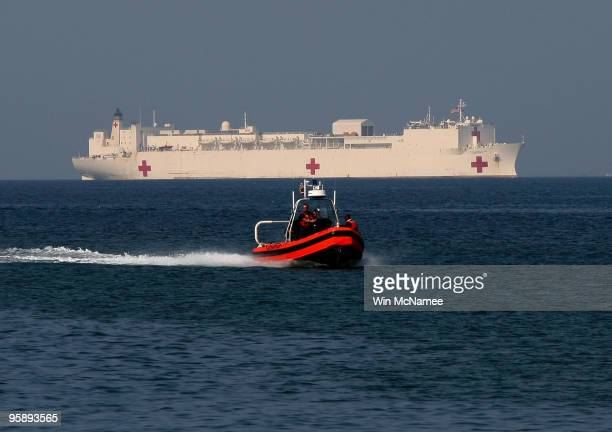 A small boat pilots in front of the USNS Comfort a floating medical treatment facility iin the harbor of PortauPrince January 20 2010 in PortauPrince...