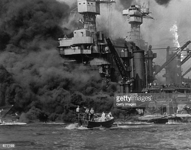 A small boat rescues sailors December 7 1941 from the USS West Virginia after she had suffered a hit in the Japanese attack on Pearl Harbor The USS...