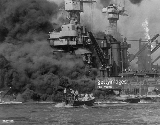 A small boat rescues sailors from the USS 'West Virginia' after she had suffered a hit in the Japanese attack on Pearl Harbor The USS Tennessee is...