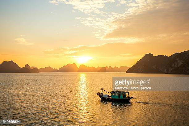 Small boat skims along as sun sets over bay with limestone formations in backgound