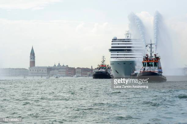 Small boat sprays water to mark the cruise ship's departure in the Gran Canal on June 05, 2021 in Venice, Italy. The first cruise ship since the...