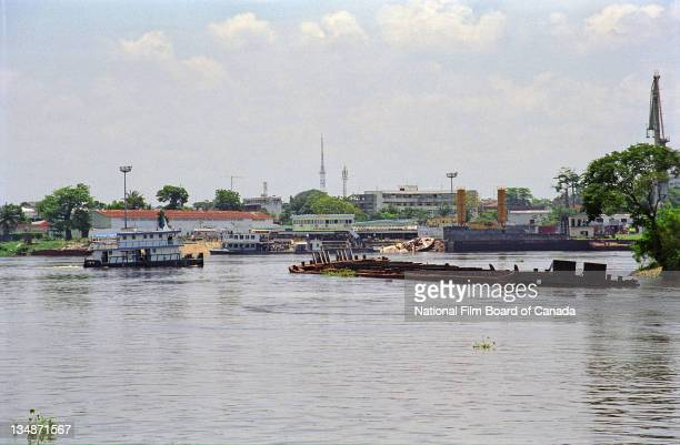 A small boat travels near a rusted and sunken shipwreck on the Congo River near Kinshasa Democratic Republic of the Congo 2003 Photo taken during the...