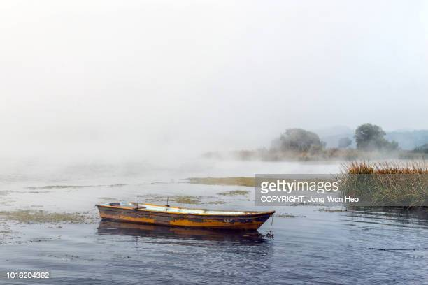A small boat voyaging around the river in the fog