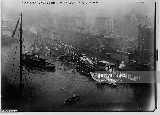 Small boats attempt to rescue survivors gathered on the exposed side of the excursion boat SS Eastland which overturned in the Chicago River.